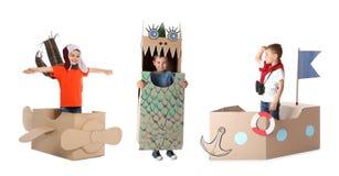 Netter kleiner Junge, der mit Pappschachteln auf Weiß spielt Handgemachte Spielwaren und Kostüme lizenzfreies stockbild