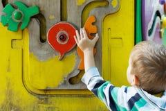 Netter kleiner Junge, der mit Spielwaren auf Spielplatz spielt lizenzfreies stockfoto
