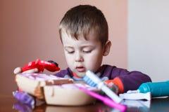 Netter kleiner Junge, der mit vielfarbigem Plasticine spielt Junge, der mit Spielwaren zahnmedizinischen Werkzeugen spielt Lustig stockfotografie