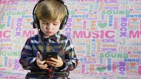 Netter kleiner Junge, der Musik in den schwarzen großen Kopfhörern hört stock footage