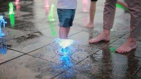 Netter kleiner Junge, der Mutterhand hält und mit Wasserstrahl am Brunnen am heißen Sommertag spielt stock video footage