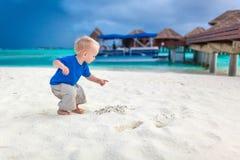 Netter kleiner Junge, der nach Schatz auf dem tropischen Strand sucht lizenzfreies stockfoto