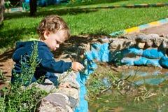 Netter kleiner Junge, der nahe dem Teich spielt Stockfoto