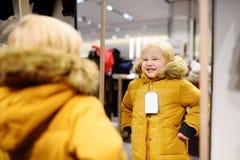 Netter kleiner Junge, der neuen Mantel während des Einkaufens versucht stockbild
