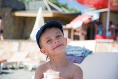 Netter kleiner Junge, der am Ozeanstrand ein Sonnenbad nimmt Lizenzfreie Stockfotografie