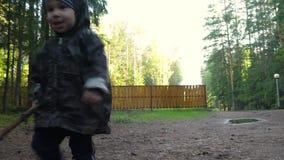 Netter kleiner Junge, der in Park geht, Spaß hat und mit dem Stock, laufend seine Mutter spielt nach stock video footage