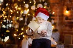 Netter kleiner Junge, der Sankt-Hut öffnet ein Weihnachtsgeschenk trägt lizenzfreie stockfotos