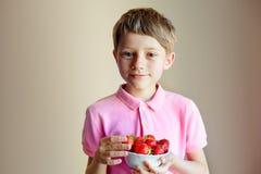 Netter kleiner Junge, der Schüssel mit Erdbeeren hält Lizenzfreie Stockfotos