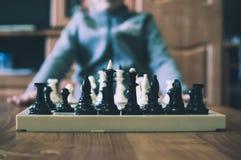 Netter kleiner Junge, der Schach spielt stockfotografie