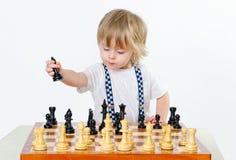 Netter kleiner Junge, der Schach spielt Stockfotos
