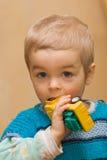 Netter kleiner Junge, der sein plactic Autospielzeug beißt lizenzfreies stockbild