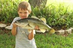 Netter kleiner Junge, der seinen Barsch vorführt Lizenzfreies Stockbild