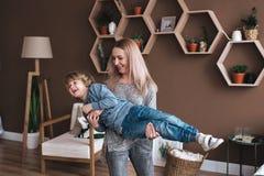 Netter kleiner Junge, der Spaß mit Mutter auf Sofa hat lizenzfreie stockfotos
