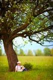 Netter kleiner Junge, der unter dem großen blühenden Birnenbaum, Landschaft sitzt Stockbild