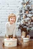 Netter kleiner Junge, der unter dem Weihnachtsbaum mit Geschenkbox sitzt Stockfotos