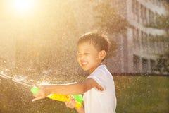 Netter kleiner Junge, der Wasserwerfer im Park spielt Stockbild