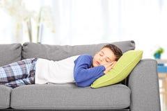 Netter kleiner Junge, der zuhause auf Sofa schläft Stockbild