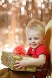 Netter kleiner Junge des blonden Haares hält ein Geschenk lizenzfreie stockfotografie