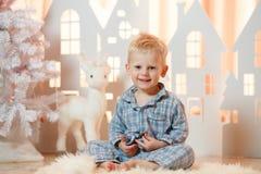 Netter kleiner Junge des blonden Haares im Sleepwear nahe Weihnachtsspielzeug-Papierhäusern stockfotografie