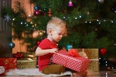Netter kleiner Junge des blonden Haares nahe dem Kamin und den Geschenken unter Weihnachtsbaum stockbild
