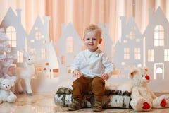 Netter kleiner Junge des blonden Haares nahe Weihnachtsspielzeug-Papierhäusern stockbild