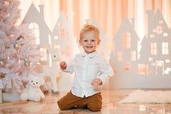 Netter kleiner Junge des blonden Haares nahe Weihnachtsspielzeug-Papierhäusern stockfotografie