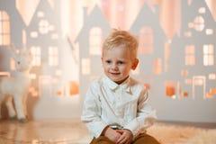 Netter kleiner Junge des blonden Haares nahe Weihnachtsspielzeug-Papierhäusern stockbilder