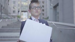 Netter kleiner Junge des Porträts in einem Anzug und Gläsern, die draußen einen Kasten mit Briefpapier auf der Treppe halten Kind stock video