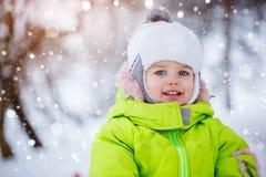 Netter kleiner Junge des Porträts unter dem Schnee, Winterzeit, Glückkonzept Stockfotos