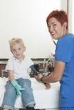 Netter kleiner Junge Doktors Examining Stockfoto