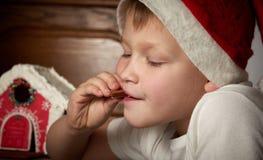 Netter kleiner Junge in einem Weihnachtshut isst Ingwerplätzchen stockfotografie