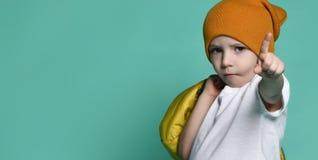 Netter kleiner Junge im weißen T-Shirt, im Hut und in der Jacke in seiner Hand, die vor grün-blauer Wand aufwirft stockfoto