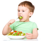 Netter kleiner Junge isst Gemüsesalat lizenzfreie stockbilder