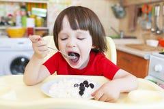 Netter kleiner Junge isst Quark mit Beere Stockfotografie