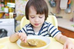 Netter kleiner Junge (2 10 Jahre) isst Erbsensuppe mit gebackenen Broten Lizenzfreie Stockfotografie