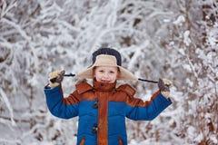 Netter kleiner Junge, Kind im Winter kleidet das Gehen unter den Schnee im Winterpark Stockfotografie