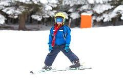 Netter kleiner Junge, lernend, im österreichischen Skiort Ski zu fahren Lizenzfreie Stockbilder