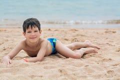 Netter kleiner Junge liegt auf dem Sand auf der glücklichen Küste, Lizenzfreie Stockbilder