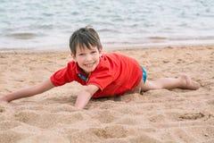 Netter kleiner Junge liegt auf dem Sand auf der glücklichen Küste, Lizenzfreies Stockfoto