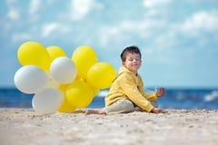 Netter kleiner Junge mit Ballonen auf dem Strand Stockbilder