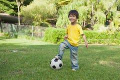 Netter kleiner Junge mit dem Fußball, der am Park steht Lizenzfreie Stockfotos