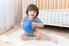 Netter kleiner Junge mit Eignungsball zuhause Stockbild