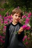 Netter kleiner Junge mit einem Blumenstrauß der Blumen Stockfotos