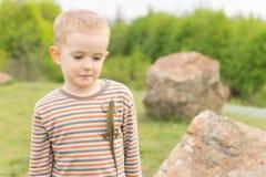 Netter kleiner Junge mit einer Eidechse auf seinem Kasten Stockbild