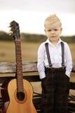 Netter kleiner Junge mit Gitarre Stockfoto