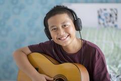 Netter kleiner Junge mit Kopfhörer und Gitarre Stockfoto