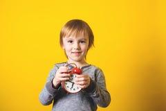 Netter kleiner Junge mit Wecker auf gelbem Hintergrund Stockbild