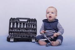 Netter kleiner Junge mit Werkzeugkasten und justierbarem Schlüssel in seinen Händen Horizontale Atelieraufnahme Stockfoto