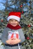 Netter kleiner Junge mit Winterwald des Weihnachtsgeschenks im Stockbild