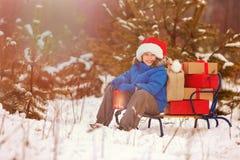 Netter kleiner Junge in Sankt-Hut trägt einen hölzernen Schlitten mit Geschenken im schneebedeckten Wald Stockfotos